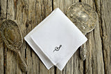 White linen handkerchief with hand embroidered initial between silver mirror and brush