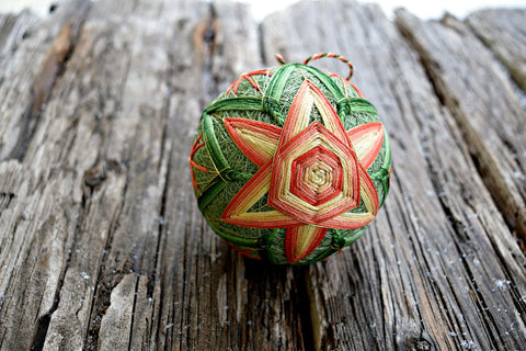 Japanese temari ball embroidered in coral and soft green in six petal flower design