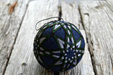 Dark blue temari embroidered in grey, green, and brown stars