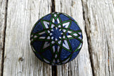 Navy temari ball embroidered with all over kiku design in grey, green, and brown