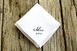 White linen handkerchief embroidered with Mrs. 6.17.17 in black on wood background