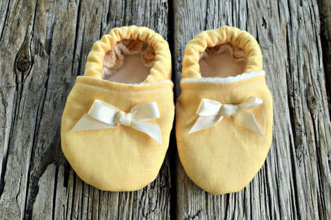 Front view of lined yellow linen baby booties with ribbon bows
