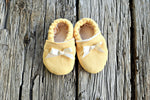 Top down view of yellow linen baby booties with cream colored lining and ribbon bows