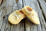 Pair of newborn baby booties in yellow with cream bows