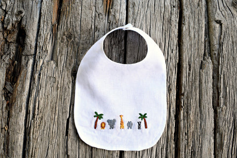 White linen baby bib embroidered with tiny safari animals between two palm trees