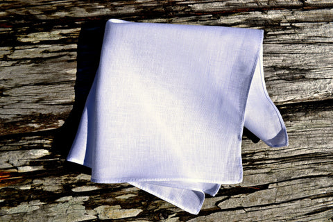 White Irish linen handkerchief with narrow rolled hem on wood background