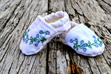 Pair of baby shoes hand embroidered with forget-me-nots