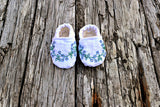 Baby shoes hand embroidered with flowers on wood background