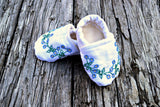 White baby booties hand embroidered with tiny flowers on wood ground