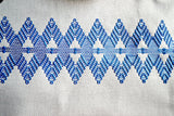 Closeup of blue diamond huck design on white tea towel