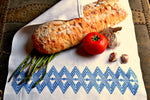 White kitchen towel with blue diamonds wrapping bread, asparagus, tomato and garlic