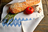 White tea towel embroidered in blue showing back of work as well as bread and veggies
