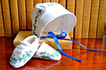 Baby bonnet and booties hand embroidered with flowers in front of books