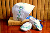 Side view of newborn christening bonnet and booties hand embroidered with flowers
