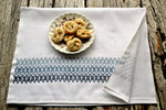 hand embroidered tea towel in geometric pattern with plate of cookies