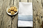 Huck embroidered tea towel in shades of soft blues