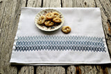 Huckaback tea towel embroidered in soft blues with dish of cookies