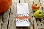 Huck teatowel stitched in fall colors with apples and pumpkin