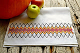 Tea towel decorated with a band of embroidery in autumnal colors