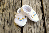 White linen baby booties stitched with little yellow ducks