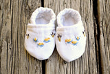 Pair of newborn slippers embroidered with small ducks and cattails, top down