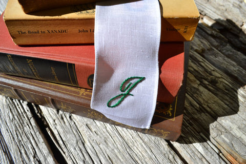 Hand embroidered white linen bookmark with script initial in stack of books
