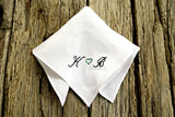 Folded Irish linen handkerchief embroidered with initials on wood ground