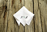 Folded white linen pocket square with initials and heart in copperplate script