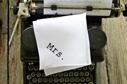 White linen handkerchief hand embroidered with Mrs. in typeset font on top of typewriter