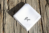 White Irish linen handkerchief embroidered with 'Papa' on a wood background