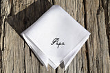 White linen hankie on wood ground, monogrammed with 'Papa'