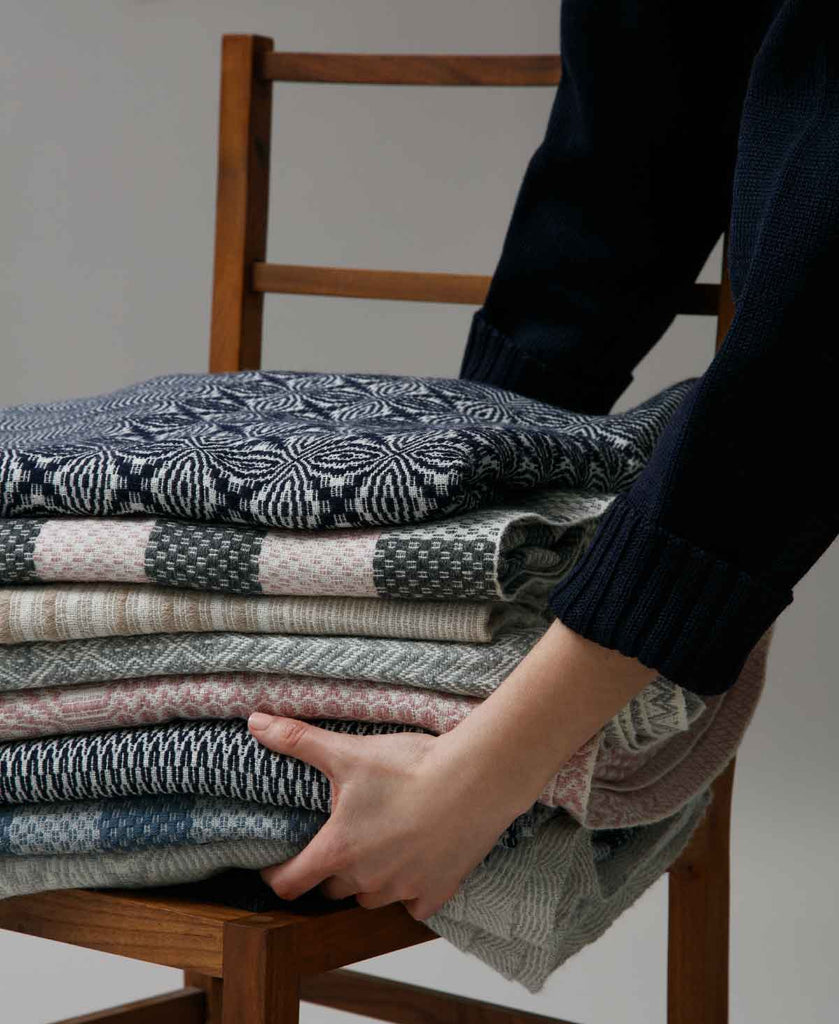 stack of vaeven coverlets being placed onto wooden chair