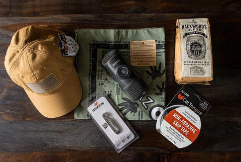 Scarf, hat, coffee, grip tape, and other camping list essentials.