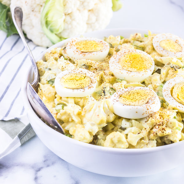 Cauliflower Potato Salad topped with hard boiled egg slices in a white bowl with a spoon