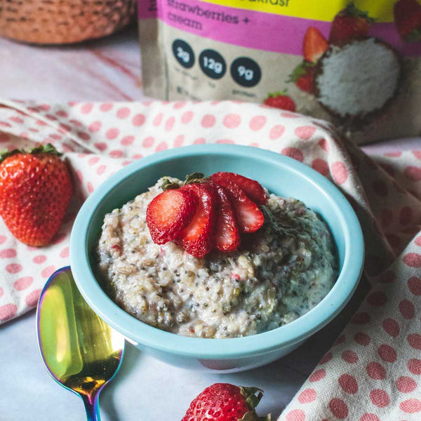 Bowl of Strawberries + Cream Instant Hot Cereal with fresh strawberries.