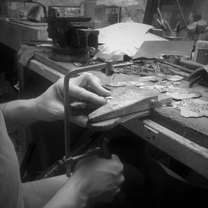 LoraLeeArtist. Using a jewelers saw to cut metal designs. Ladysmith. Metalsmith. Jewelers Bench.