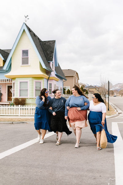 four well dressed plus-size women walk arm in arm crossing the street, in front of a colorfully painted house.