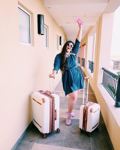 Plus-size woman, Anabeth, poses with her two suitcases while on vacation.