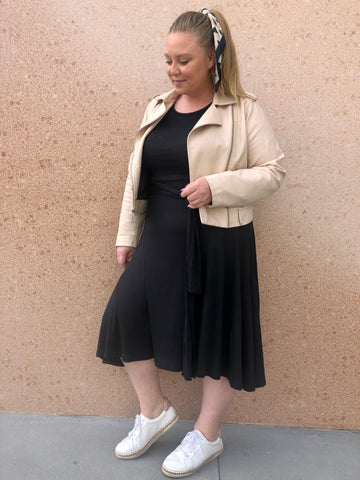 Ashby wears the Everywhere Midi Dress in black with a blush pink moto jacket and white sneakers with a silk scarf in her ponytail.