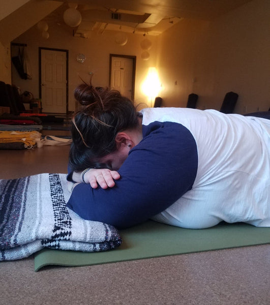 Andrea, plus-size yogi, is in crocodile pose with a blanket under her arms.