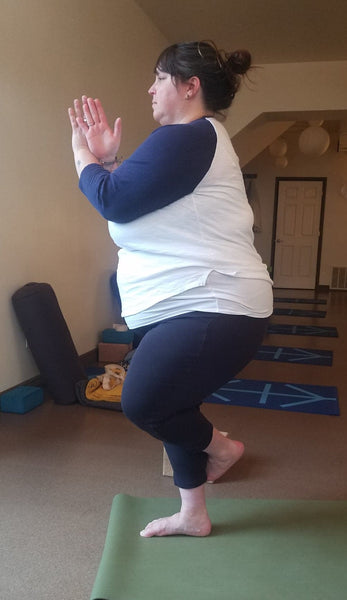 Andrea, plus-size yogi, shows a variation for eagle arms and eagle legs.