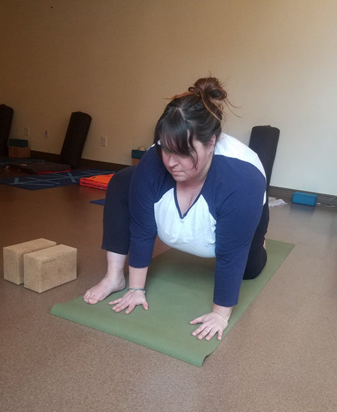Andrea is a plus-size yogi offering a modification for low lunge by bringing her front foot to the outside of the mat and placing her hands inside her front leg.