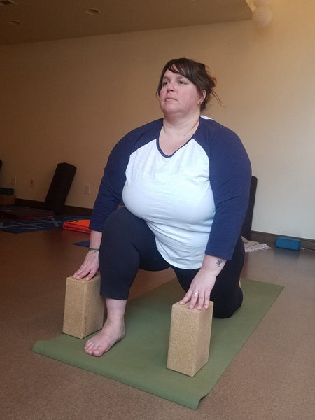 Andrea's a plus-size yogi who is demonstrating how to modify a low lunge with blocks so her hands have a place to rest.