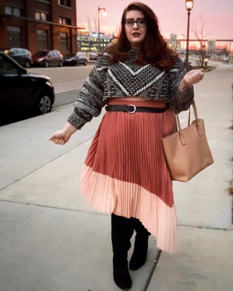 Noelle wears a chunky cropped sweater with a chevron print, with knee-high boots and a belt at the waist.