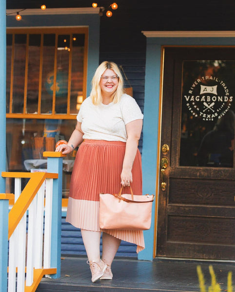 Katie Morton wears the Ori Pleated Midi Skirt in Rose and the Ori Perfect Tee in White along with pink sneakers and tote