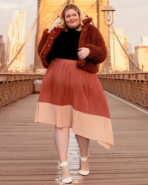 Sean wears the Ori Pleated Midi Skirt in Rose with a black turtleneck, brown teddy coat, and white ankle strap pumps on the Brooklyn Bridge at sunset.