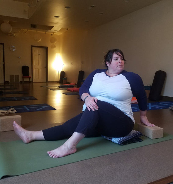 Andrea, plus-size yogi, demonstrates a variation for the seated twist yoga pose.