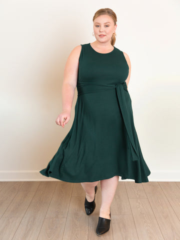 Model Ashby wears the Everywhere Dress in Deep Forest Green with black booties.