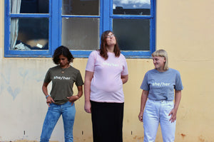 Three girls wearing pronoun tshirts
