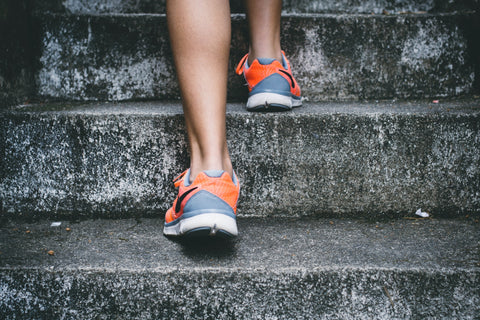 person wearing colorful shoes running up stairs